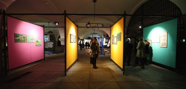 Wystawa w Akademii Sztuk Pięknych w Gdańsku, ekrany ustawione prostopadle do widza od lewej różowy, dwa żółte i zielony, poiedzy nimi zwiedzający; na ekranach wiszą prace plastyczne;