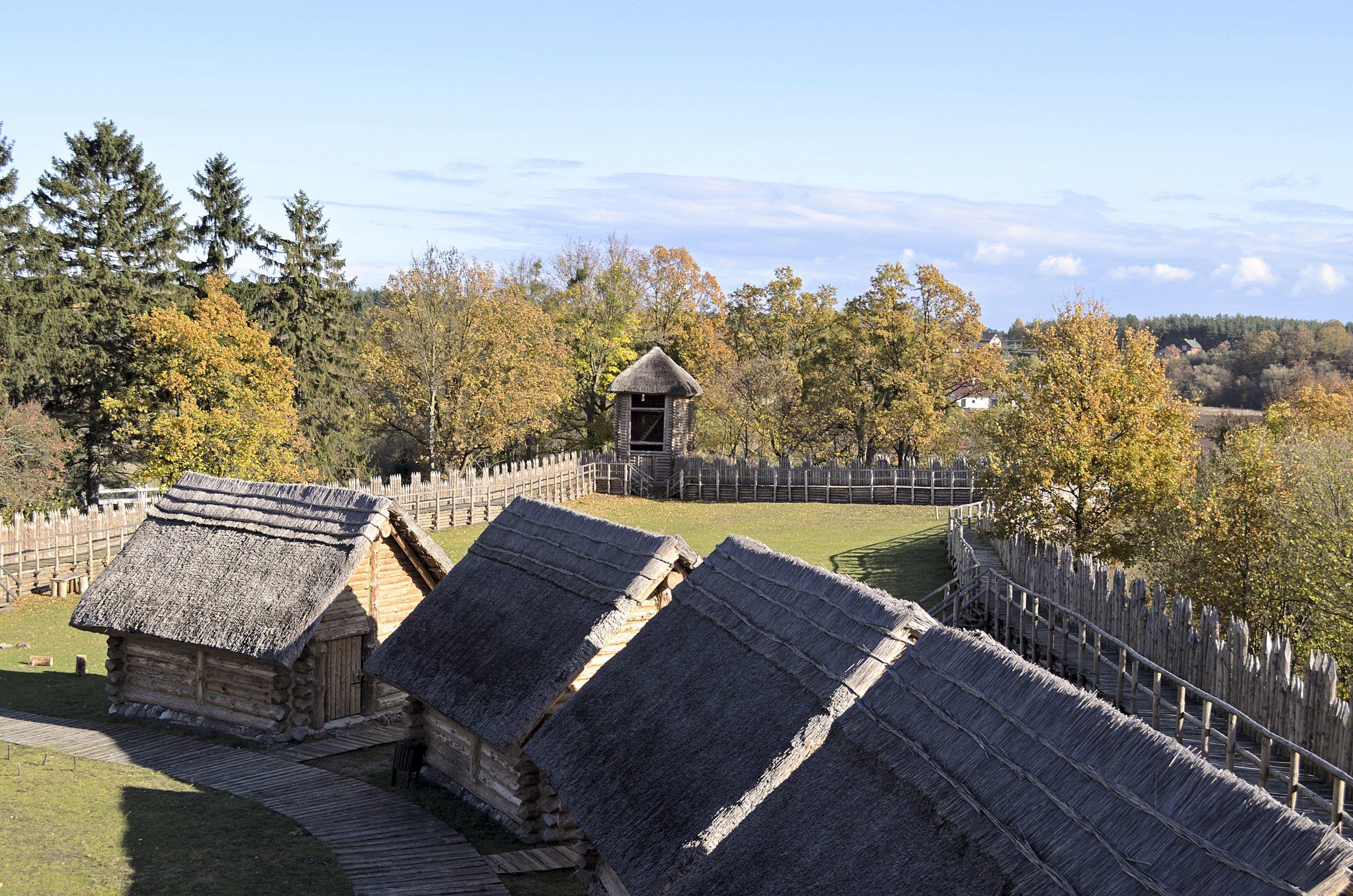 Widok z góry na drewniane dachy chat w grodzisku w Owidzu.